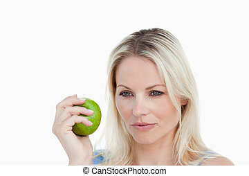 Thoughtful blonde woman holding a green apple
