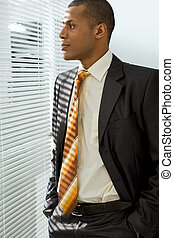 Thoughtful boss - Serious businessman standing and looking ...