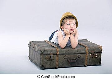 Thoughtful boy lying on the suitcase