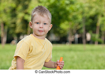 Thoughtful boy with a carrot