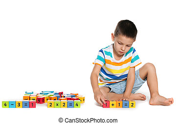 Thoughtful boy with blocks on the floor