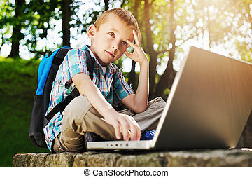 Thoughtful boy with laptop