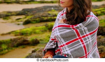 Thoughtful brunette wrapped in a blanket sitting by the...