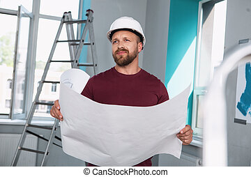 Thoughtful builder holding a big sketch