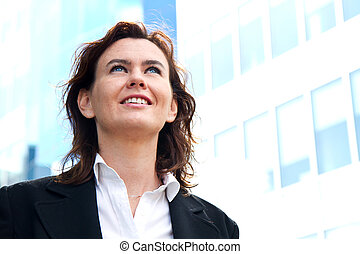 Thoughtful business woman looking up and smiling