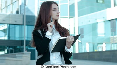 thoughtful business woman makes notes in a Notepad