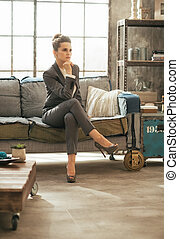 Thoughtful business woman sitting on divan in loft apartment