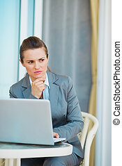 Thoughtful business woman working with laptop on terrace