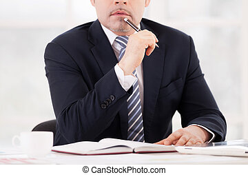 Thoughtful businessman. Cropped image of thoughtful senior man in formalwear holding pen on chin while sitting at his working place