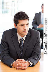 Thoughtful businessman during a meeting with a colleague