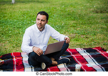 Thoughtful businessman in the field. With laptop