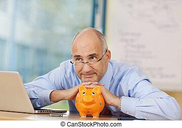 Thoughtful Businessman Leaning On Piggybank At Desk