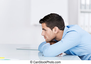 Thoughtful Businessman Looking Away While Leaning On Desk