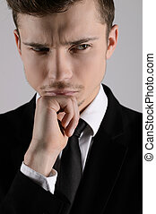 Thoughtful businessman. Portrait of businessman holding hand on chin and looking away while standing isolated on grey