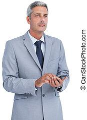 Thoughtful businessman sending text message