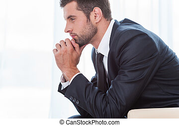 Thoughtful businessman. Side view of thoughtful young businessman in shirt and tie holding hands on chin and looking away while sitting at the chair
