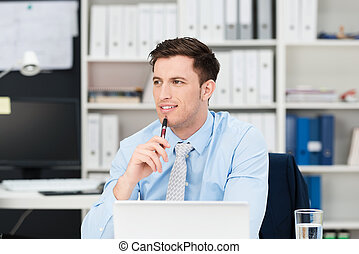 Thoughtful businessman sitting at his desk