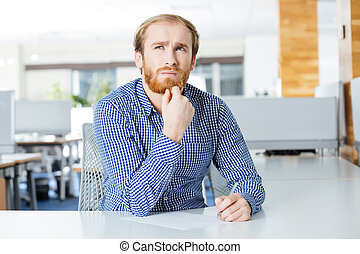 Thoughtful businessman sitting at the table in office and writing