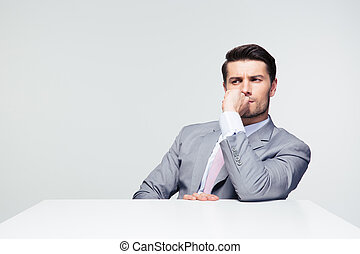 Thoughtful businessman sitting at the table