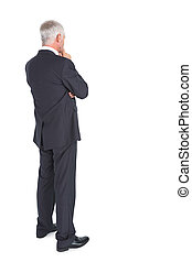 Thoughtful businessman standing back to camera