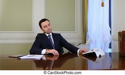 Thoughtful businessman thinking and answering landline...