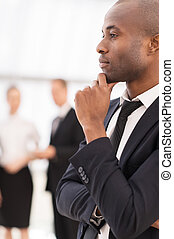 Thoughtful businessman.  Thoughtful young African man in formalwear holding hand on chin and looking away while his colleagues  standing on background