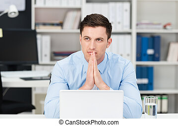 Thoughtful young businessman trying to solve a business problem sitting at his desk with his hands steepled as he stares into the distance in contemplation