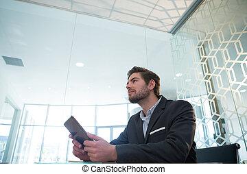 Thoughtful businessman using digital tablet at desk