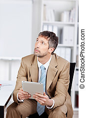 Thoughtful Businessman Using Digital Tablet In Office