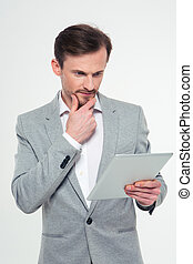 Thoughtful businessman using tablet computer