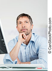 Thoughtful Businessman With Computer At Desk