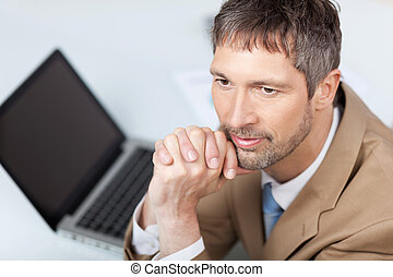 Thoughtful Businessman With Laptop At Desk