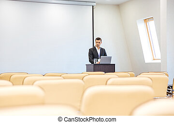 Thoughtful businessman with laptop in empty conference hall