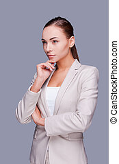 Thoughtful businesswoman. Confident young businesswoman holding hand on chin and looking away while standing against grey background