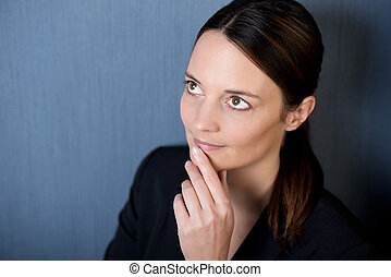Thoughtful Businesswoman Looking Up Against Blue Wall