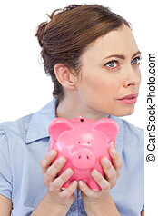 Thoughtful businesswoman posing with piggy bank in close up