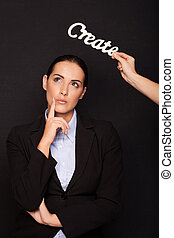 Thoughtful businesswoman standing under CREATE