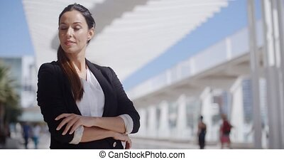 Thoughtful businesswoman with folded arms