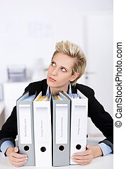 Thoughtful Businesswoman With Ring Binders At Desk