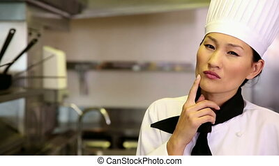 Thoughtful chef smiling at camera in commercial kitchen