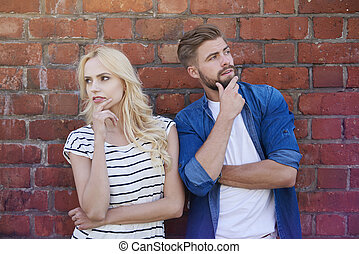 Thoughtful couple and the brick wall