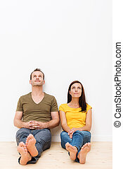 Thoughtful couple sitting on a wooden floor
