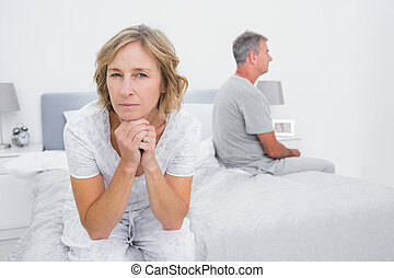 Thoughtful couple sitting on different sides of bed having a dispute with woman looking at camera in bedroom at home