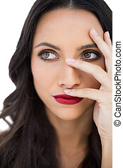Thoughtful dark haired woman with red lips hiding her face