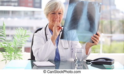 Thoughtful doctor holding an x-ray