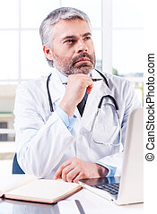 Thoughtful doctor. Thoughtful mature grey hair doctor holding hand on chin and looking away while sitting at his working place