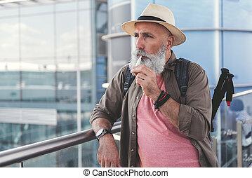 Thoughtful elder male tourist smoking
