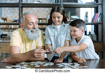 Thoughtful elderly man and grandchildren putting puzzle together