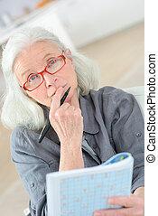 thoughtful elderly woman doing crossword