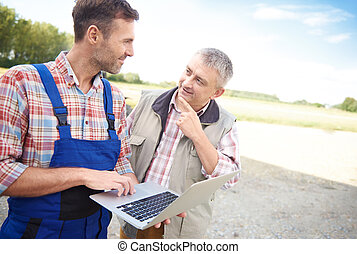 Thoughtful farmers talking over laptop